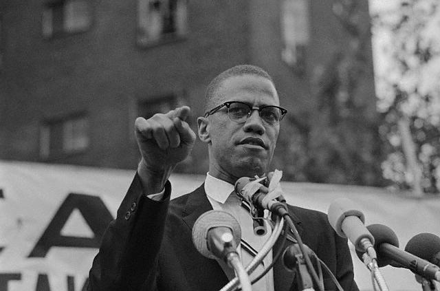 Malcolm X Shown with a Clenched Fist Speaking at a Rally